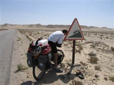 Dragging his massive pack up a mean hill in the Sahara