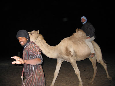 Cecil riding a camel in Mauritania